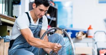 Fahrrad Routen: Mechaniker prüft Schaltung eines Fahrrads